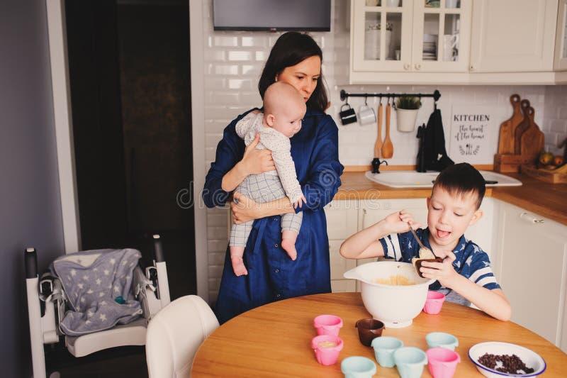 Gelukkig familiebaksel samen in moderne witte keuken Moeder, zoons en babydochter het koken in comfortabele weekendochtend stock afbeeldingen