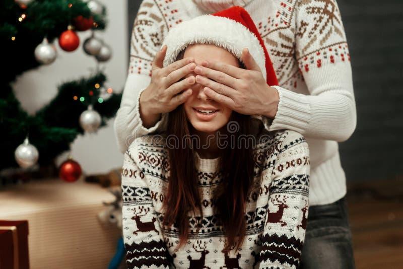 Gelukkig familiepaar, knappe mens die aanwezige Kerstmis voorbereiden stock afbeelding