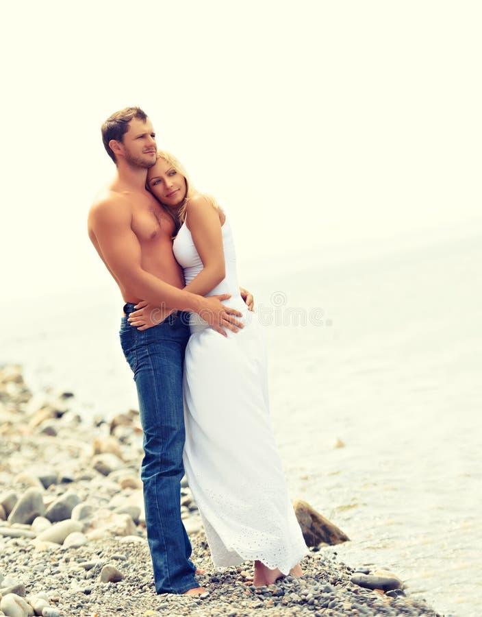 Gelukkig familiepaar in liefde die en op het strand koesteren lachen royalty-vrije stock foto