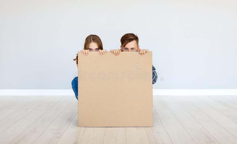 Gelukkig familiepaar met kartonaffiche op blinde muur stock afbeelding