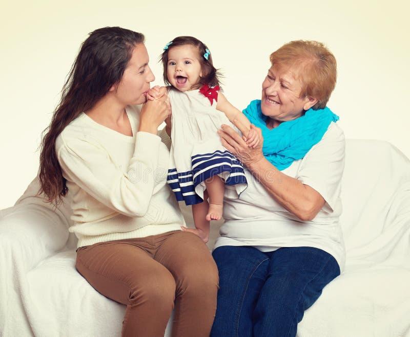 Gelukkig familieportret - baby, vrouw en oude dame op wit stock afbeelding