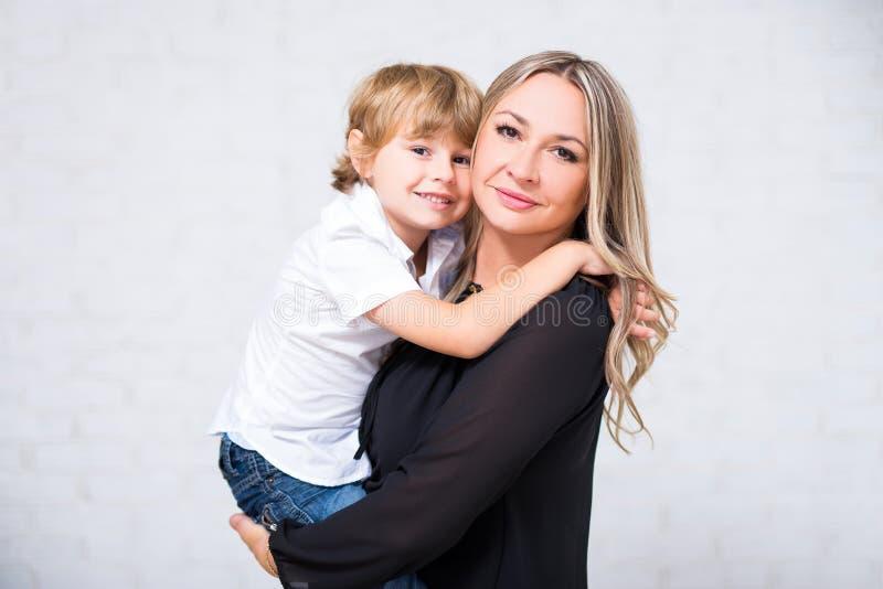 Gelukkig familieportret - leuke moeder met weinig zoon die over stellen royalty-vrije stock afbeeldingen