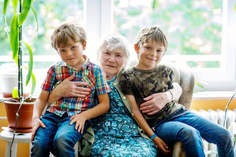 Gelukkig familieportret met grootmoeder en twee kleinzonen Grote grootmoederzitting met twee jongens van het schooljonge geitje t royalty-vrije stock afbeeldingen