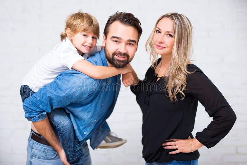 Gelukkig familieportret - paar met leuk weinig zoon over wit stock afbeelding