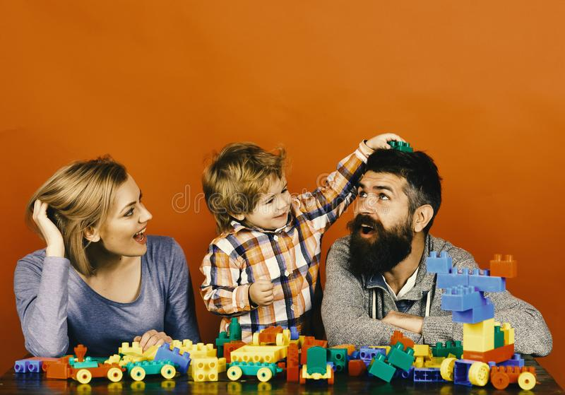 Gelukkig familiespel De familie met vrolijke gezichten bouwt uit gekleurde bouwblokken royalty-vrije stock fotografie