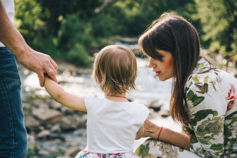 Gelukkig familiespel met dochter dichtbij de rivier in bergen stock afbeelding