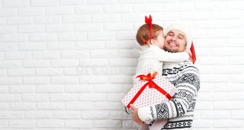 Gelukkig familievader en kind met gift in Kerstmiskus stock foto's