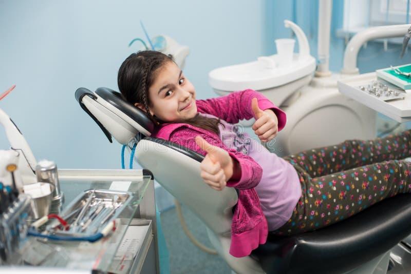 Gelukkig geduldig meisje die duimen tonen op tandkantoor Geneeskunde, de stomatologie en gezondheidszorgconcept stock afbeeldingen