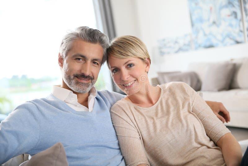 Gelukkig gehuwd paar op middelbare leeftijd thuis stock afbeeldingen