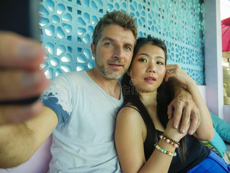 Gelukkig gemengd het behoren tot een bepaald raspaar in liefde glimlachen vrolijk met de knappe Kaukasische mens en mooie Aziatis royalty-vrije stock fotografie