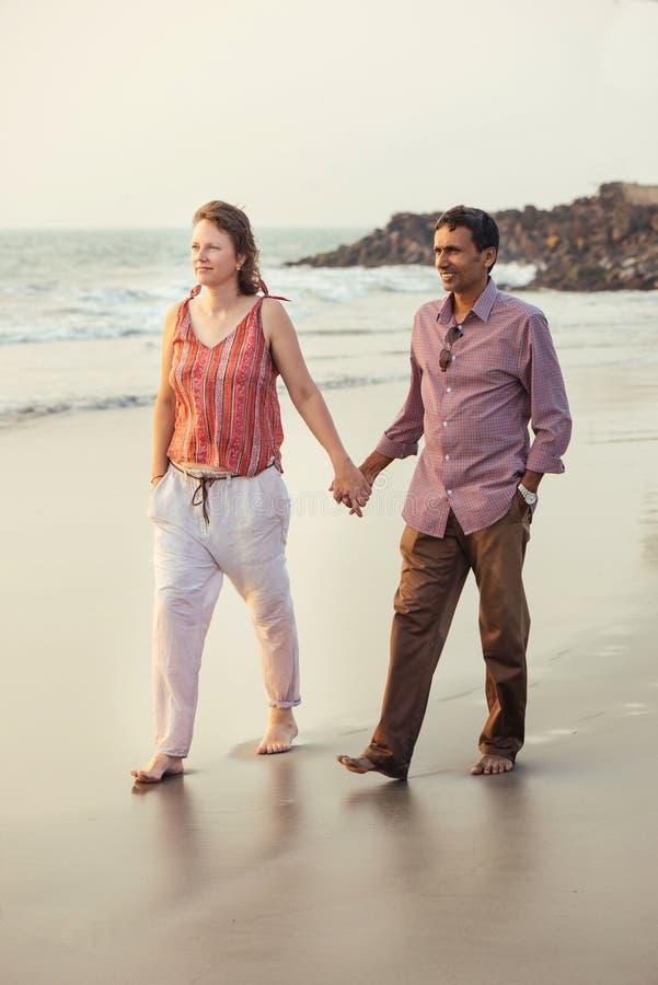 Gelukkig gemengd raspaar die op het strand lopen royalty-vrije stock foto