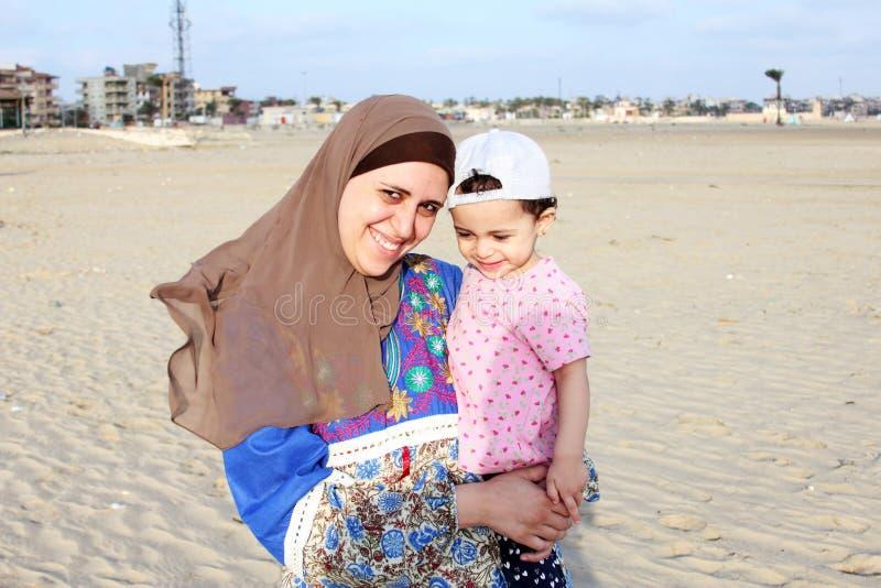 Gelukkig glimlachend Arabisch moslimbabymeisje met haar moeder stock afbeelding