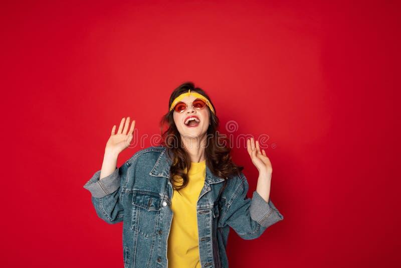 Gelukkig glimlachend die hipster meisje op rood wordt ge?soleerd stock afbeelding