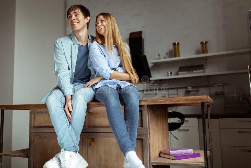 Gelukkig glimlachend jong paar in de blauwe zitting van de denimdoek in de keuken royalty-vrije stock afbeelding