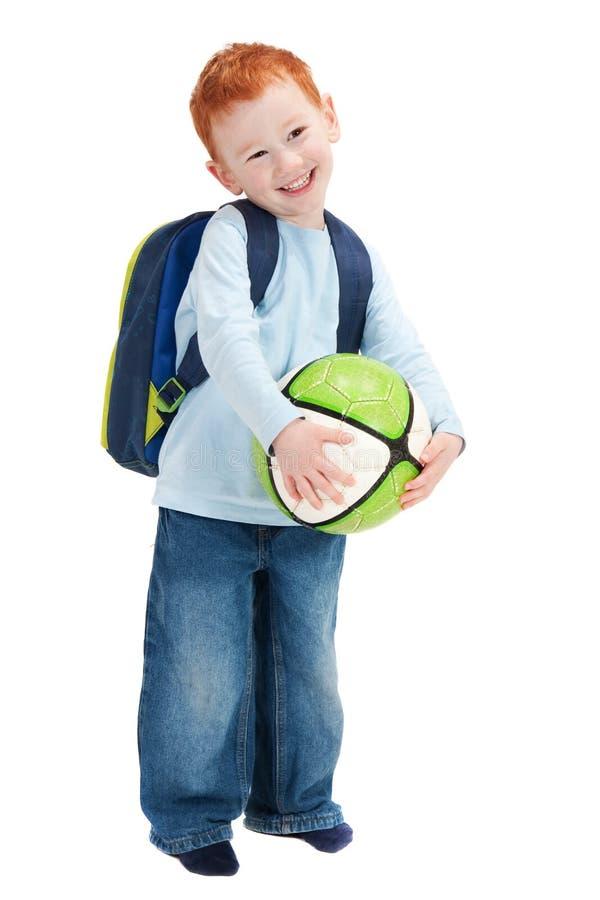 Gelukkig glimlachend jongenskind met bal en schooltas stock foto