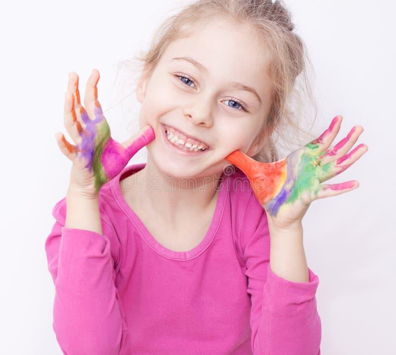 Gelukkig glimlachend kindmeisje die pret met geschilderde handen hebben royalty-vrije stock afbeeldingen