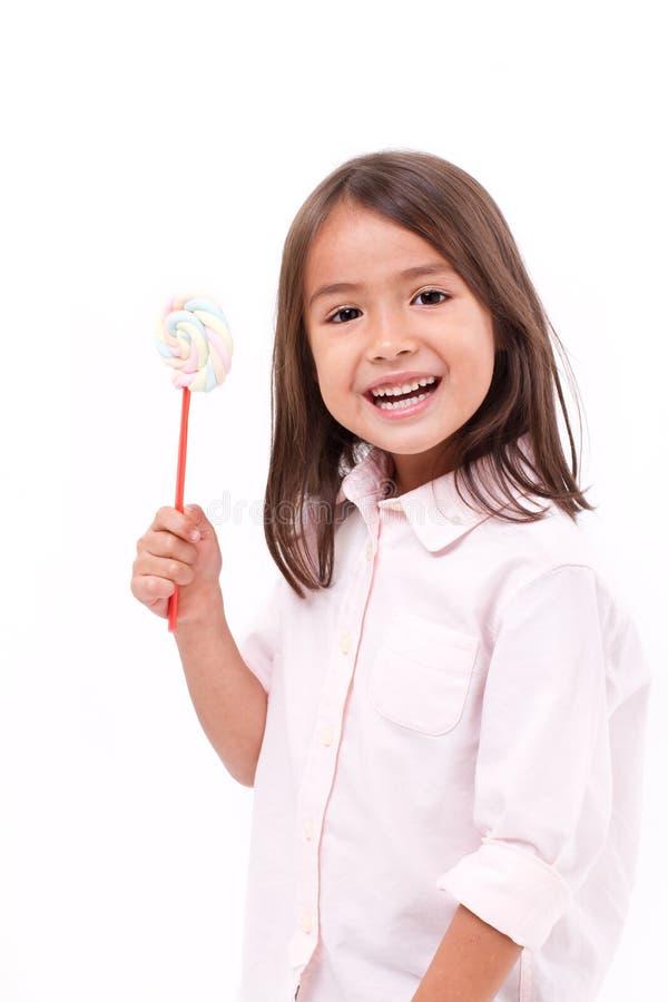 Gelukkig, glimlachend leuk meisje die heemst zoet suikergoed eten stock foto