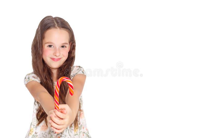 Gelukkig, glimlachend leuk meisje die het riet van het cristmassuikergoed eten Geïsoleerd op wit royalty-vrije stock foto's