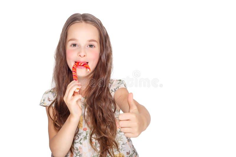 Gelukkig, glimlachend leuk meisje die het riet van het cristmassuikergoed eten Geïsoleerd op wit stock afbeeldingen