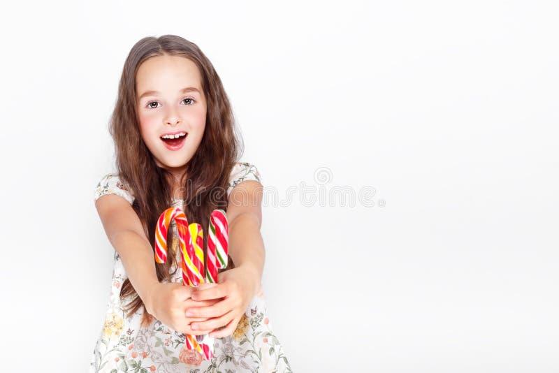Gelukkig, glimlachend leuk meisje die het riet van het cristmassuikergoed eten Het stellen tegen een witte muur stock afbeeldingen
