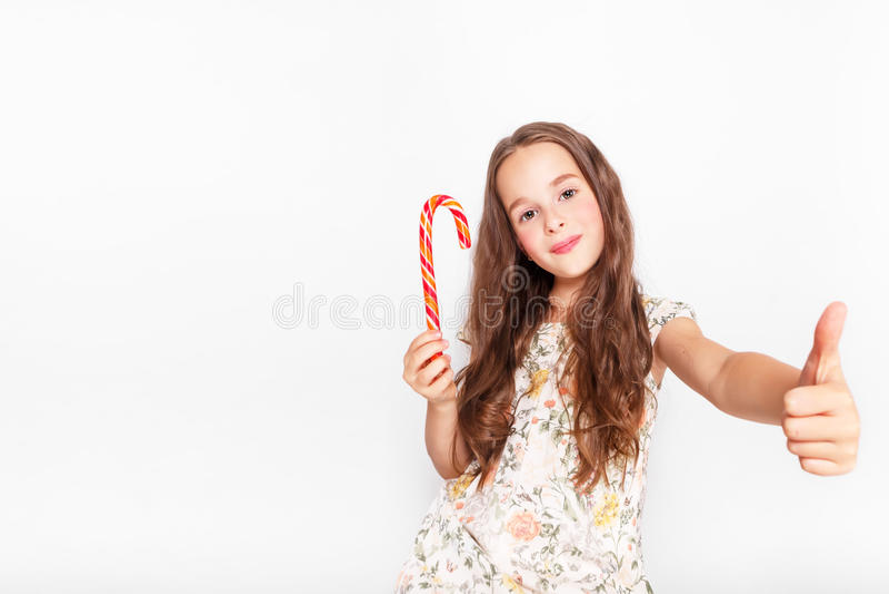 Gelukkig, glimlachend leuk meisje die het riet van het cristmassuikergoed eten Het zeggen van O.k. Het stellen tegen een witte mu stock afbeeldingen