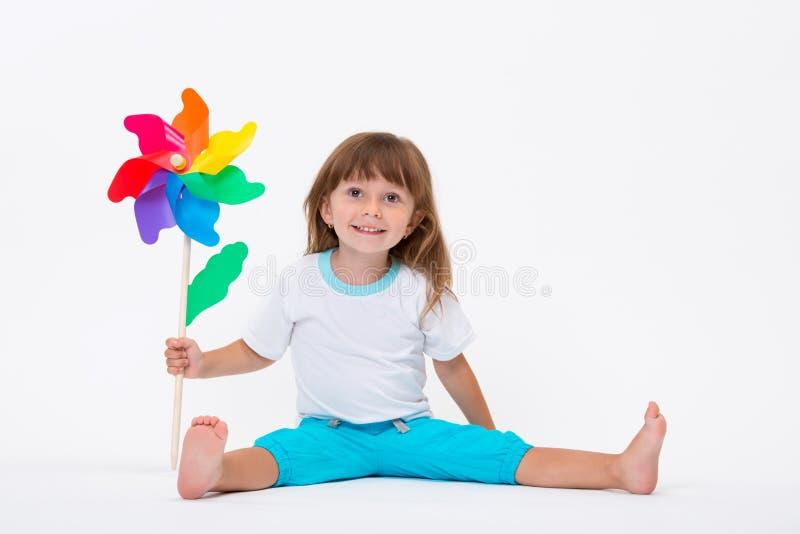 Gelukkig glimlachend meisje die een kleurrijke die stuk speelgoed vuurradwindmolen houden op witte achtergrond wordt geïsoleerd stock afbeelding