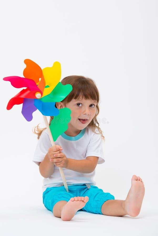 Gelukkig glimlachend meisje die een kleurrijke die stuk speelgoed vuurradwindmolen houden op witte achtergrond wordt geïsoleerd stock afbeeldingen