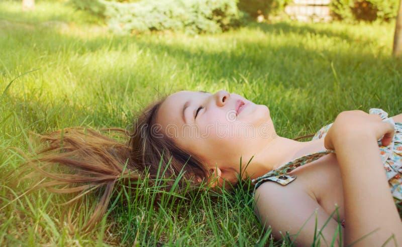 Gelukkig glimlachend meisje die op het gras in zonnige de zomerdag liggen royalty-vrije stock fotografie