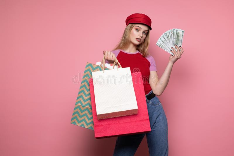 Gelukkig glimlachend meisje die in in rode hoed kleurrijke het winkelen zakken houden royalty-vrije stock afbeelding