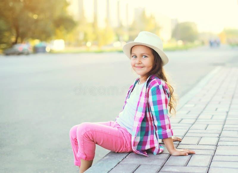 Gelukkig glimlachend meisjekind dat een geruite roze overhemd en een hoed draagt royalty-vrije stock foto