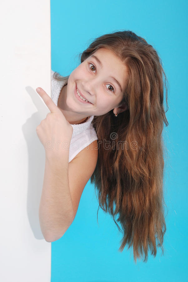 Gelukkig glimlachend mooi jong meisje die leeg uithangbord tonen of mede stock foto