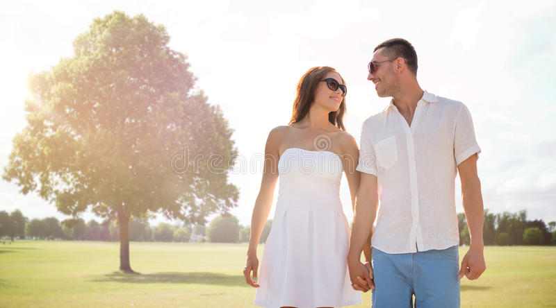Gelukkig glimlachend paar die over de zomerpark lopen stock foto's
