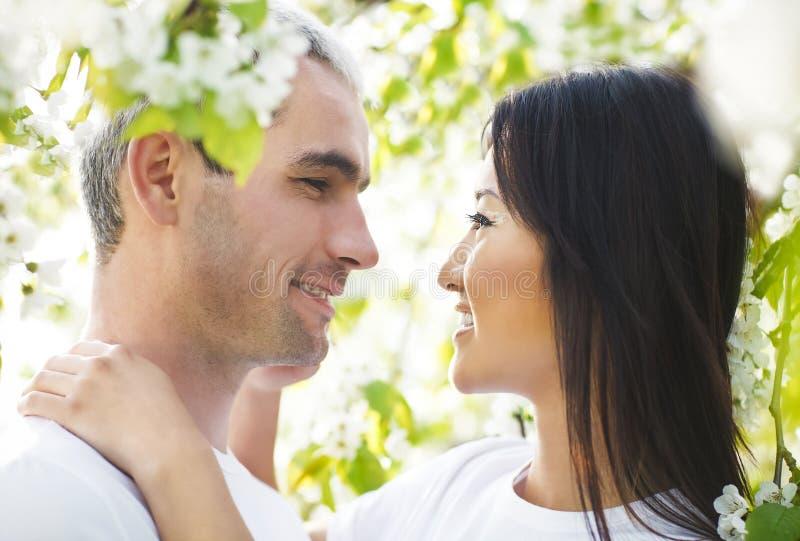 Gelukkig glimlachend paar in liefde in de lentetuin stock fotografie