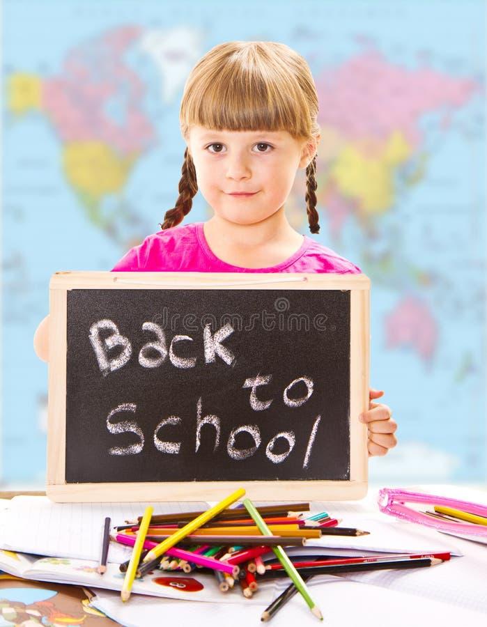 Gelukkig glimlachend schoolkind die klein bord houden royalty-vrije stock foto