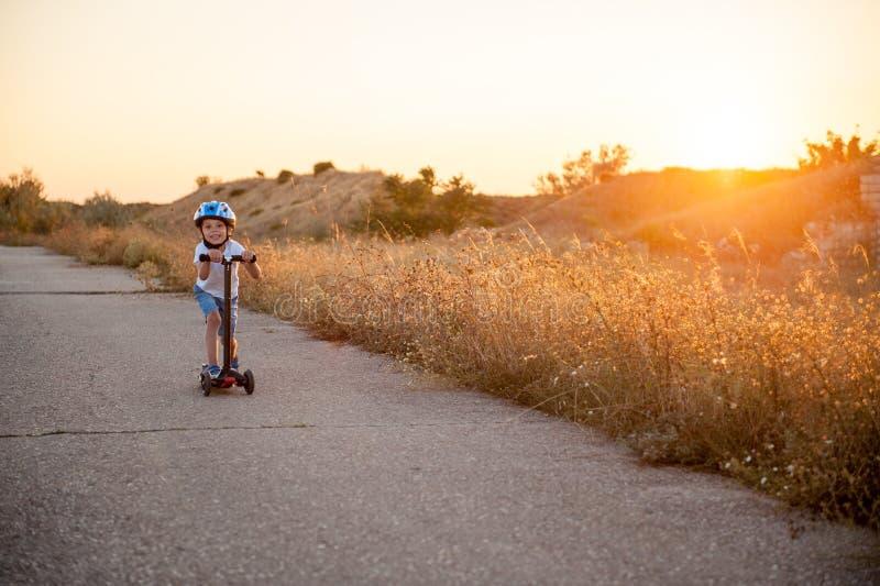 Gelukkig glimlachend weinig jongens berijdende autoped op lege weg op de zomerzonsondergang stock fotografie