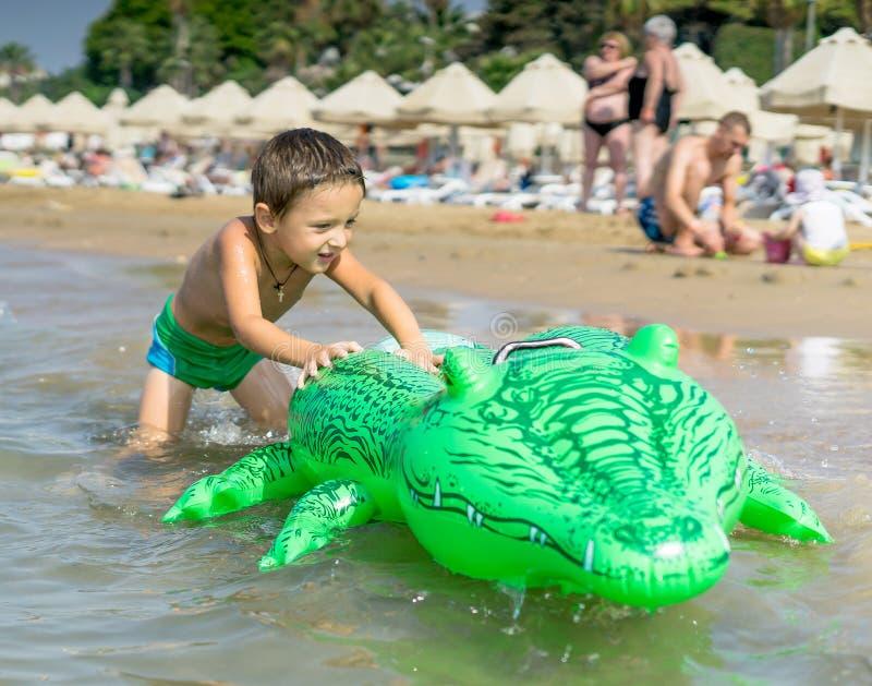 Gelukkig glimlachend weinig spel van de jongenslooppas met golven op strand Italië De zomer royalty-vrije stock afbeelding