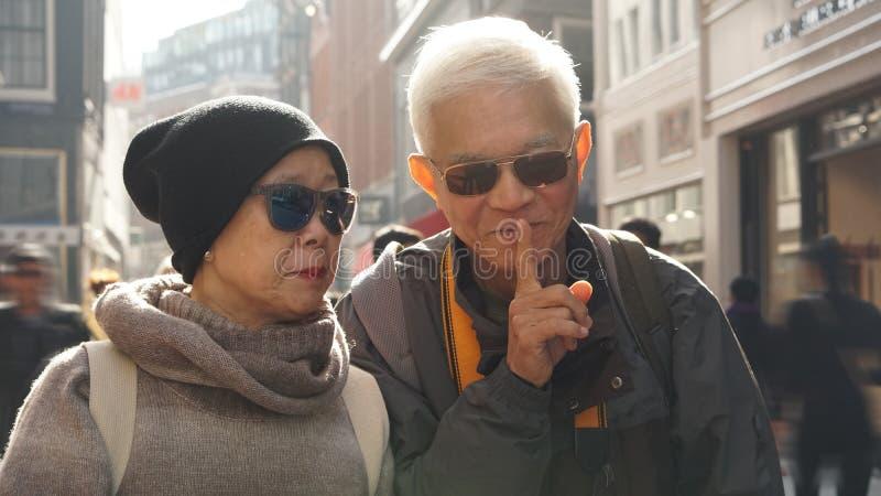 Gelukkig grappig Aziatisch hoger paar die elkaar plagen De echtgenoot vertelt royalty-vrije stock foto