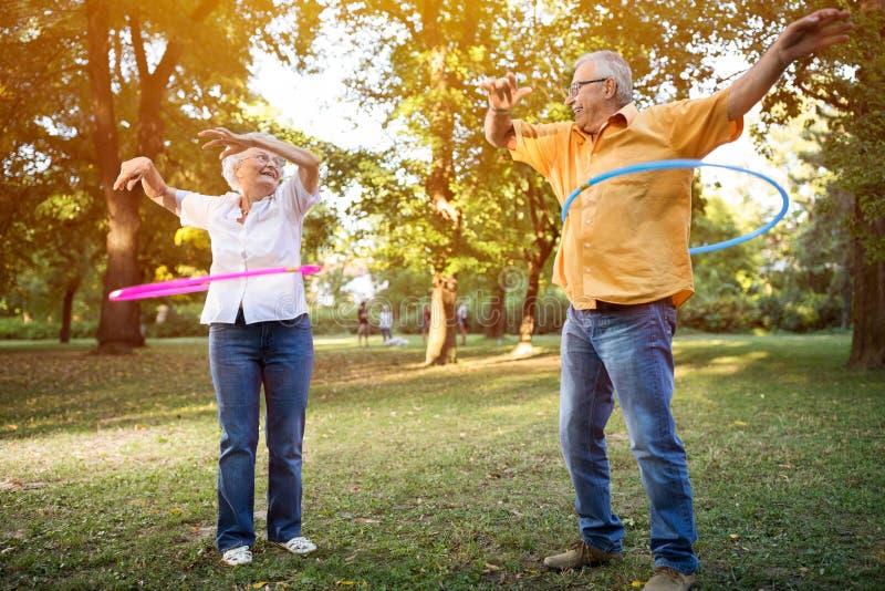 Gelukkig grappig hoger paar die hulahop in park spelen royalty-vrije stock afbeelding