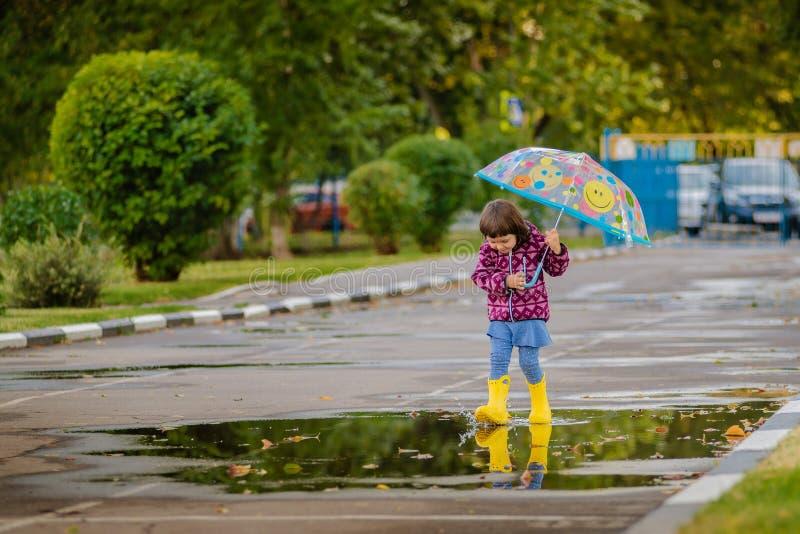 Gelukkig grappig kind met multicolored paraplu het springen vulklei in rubberlaarzen en het lachen royalty-vrije stock afbeeldingen