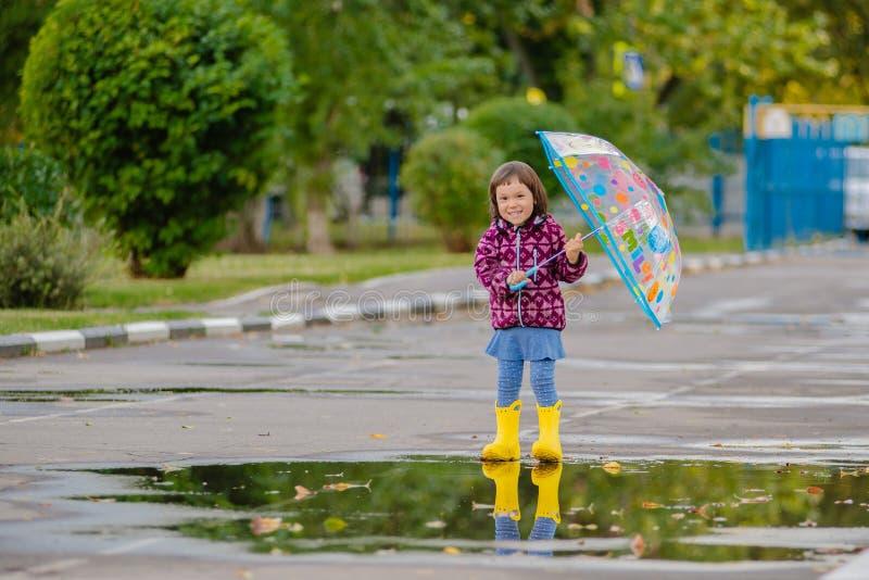Gelukkig grappig kind met multicolored paraplu het springen vulklei in rubberlaarzen en het lachen stock afbeelding