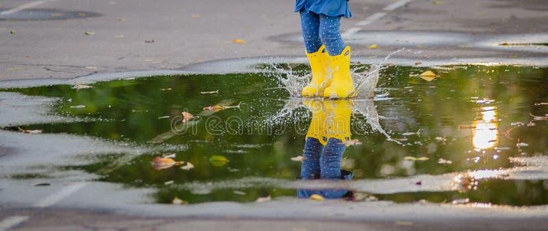 Gelukkig grappig kind met multicolored paraplu het springen vulklei in rubberlaarzen en het lachen royalty-vrije stock foto