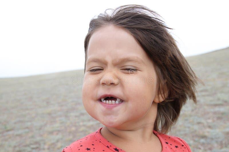 Gelukkig grappig meisje met uitdrukkingsportret De wind blaast Glimlachend zonder tanden weinig kind Het hebben van pret royalty-vrije stock fotografie