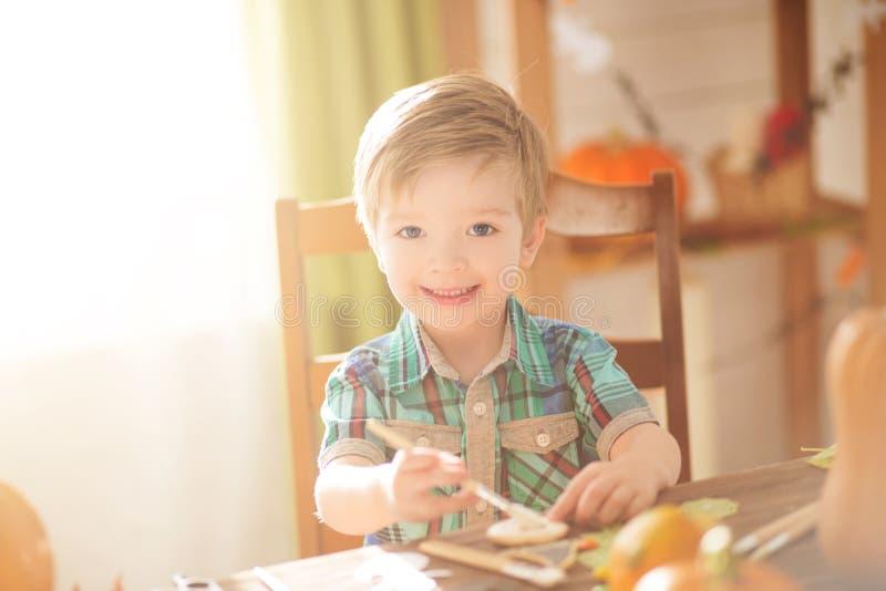 Gelukkig Halloween-concept Leuk weinig gelukkige jongen die een pompoen binnen snijden voor Halloween op een lijst royalty-vrije stock foto's