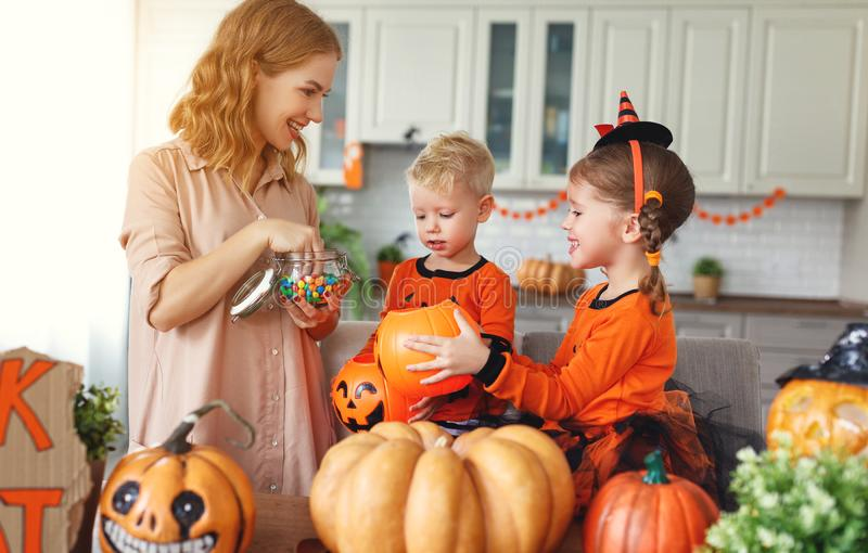 Gelukkig Halloween! de moeder behandelt kinderen thuis met suikergoed royalty-vrije stock afbeelding
