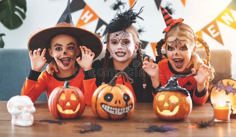 Gelukkig Halloween! een groep kinderen in kostuums en met pompoenen stock fotografie
