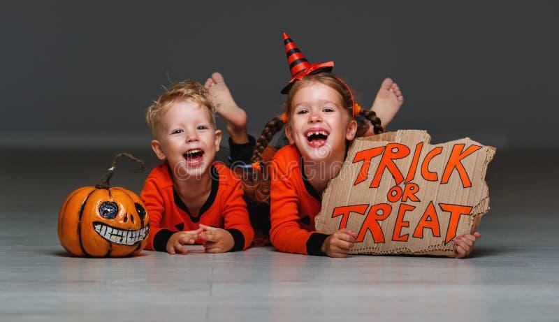 Gelukkig Halloween! vrolijke kinderen in kostuum met pompoenen op g royalty-vrije stock afbeeldingen