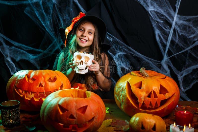 Gelukkig Halloween Weinig heksenkind met Halloween-snoepje en suikergoed met het vrolijke glimlachen over spinneweb en met stock foto's