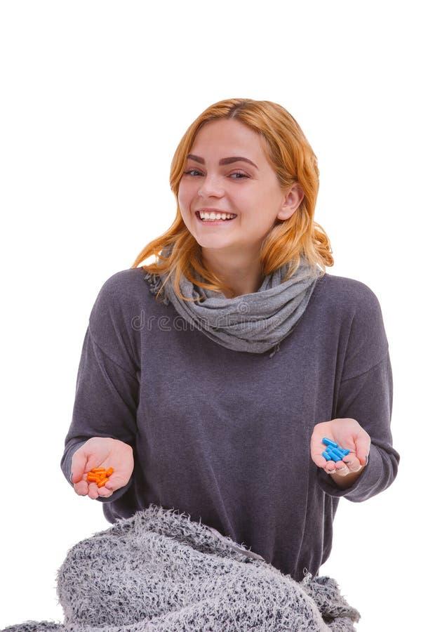 Gelukkig in handen oranje en blauwe pillen houden en meisje die, die glimlachen Geïsoleerde royalty-vrije stock fotografie