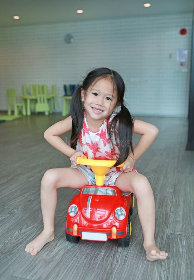 Gelukkig het glimlachen Aziatisch drijf de autostuk speelgoed van het kindmeisje bij speelkamer stock foto
