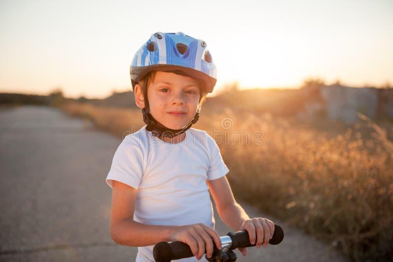 Gelukkig het glimlachen leuk gezond jong geitje in sporthelm met autoped op lege weg stock afbeeldingen